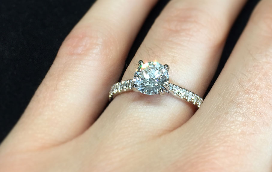 classic solitaire engagement ring set in platinum with scallop set diamond shoulders